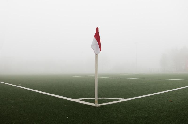 Eckfahne auf einem Fussballplatz mit Nebel