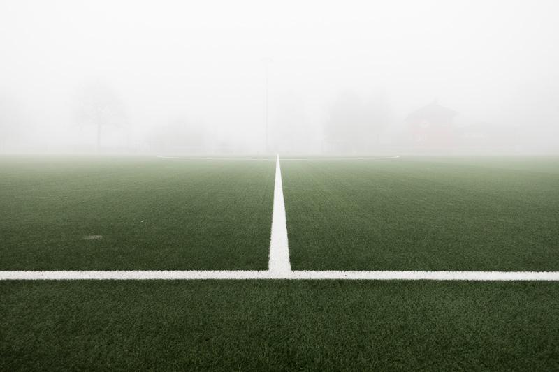 Mittellinie auf einem Fussballplatz mit Nebel