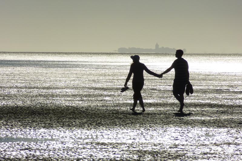 Paar am Strand, Abendstimmung, Hand in Hand