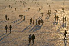 Menschenmenge auf zugefrorenen See im Abendlicht