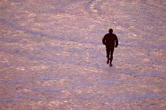 Jogger im Winter auf zugefrorenen See im Abendlicht